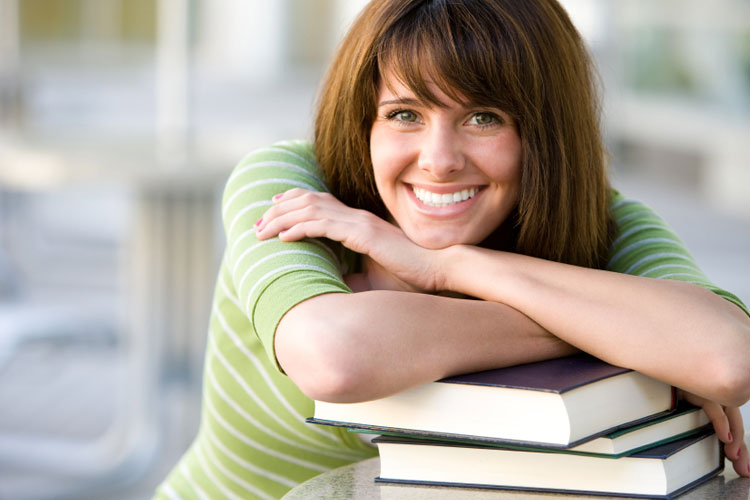 Smiling female leaning on books